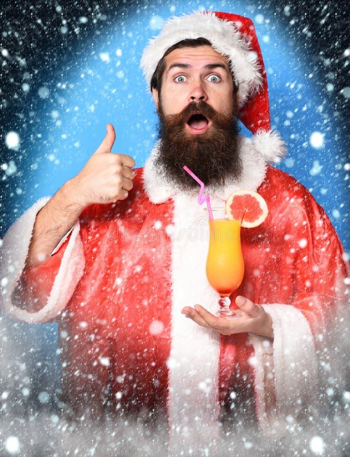 Stilig skäggig Santa Claus man med det långa skägget på hållande exponeringsglas för förvånad framsida av den nonalcoholic coctai royaltyfri bild