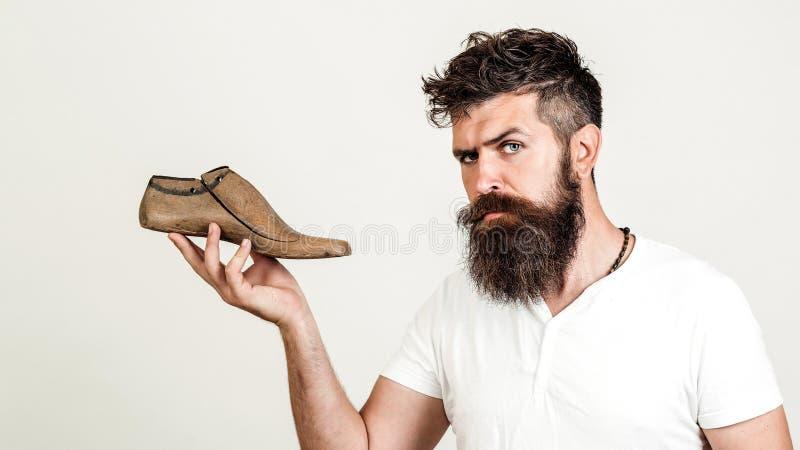 Stilig skäggig skomakare på vit bakgrund Skäggig man som rymmer den sista skon se kameran Allvarliga unga skomakareuppsättningar  royaltyfri bild