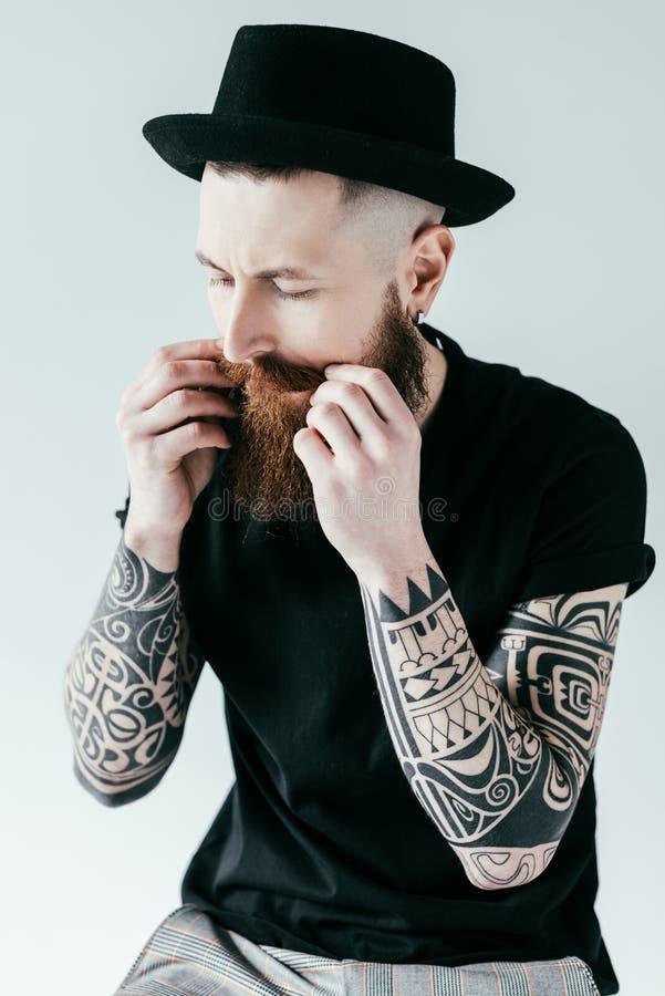 stilig skäggig tatuerad man som vrider mustaschen royaltyfri foto
