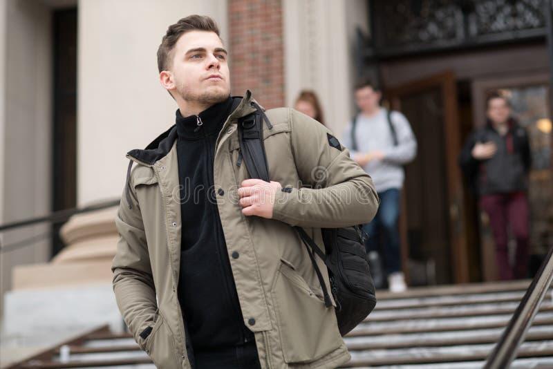 Stilig smart student som ut går från gruppen till högskolauniversitetsområdet med en ryggsäck arkivbilder