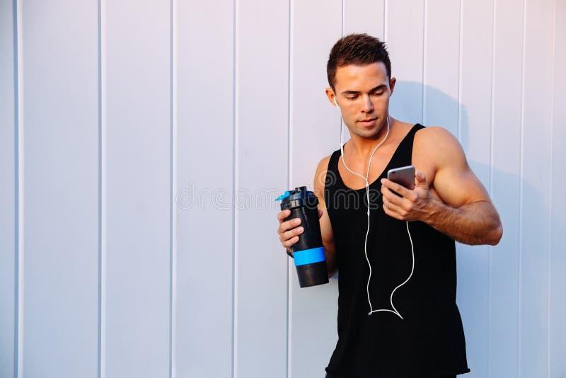 Stilig sportig man som använder en mobiltelefon som utomhus står arkivbild