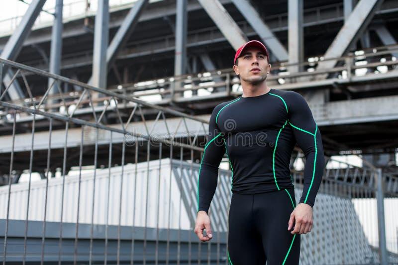 Stilig sportman i den utomhus- sportswearen, stads- Aktiv manlig yttersida på bakgrunden av bron fotografering för bildbyråer