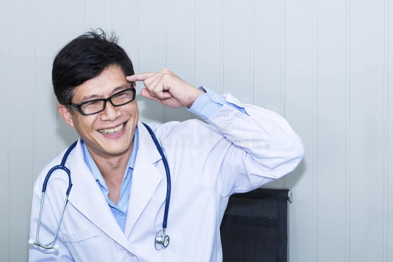 Stilig ståendeman av den mogna doktorn med det vita laget royaltyfria foton