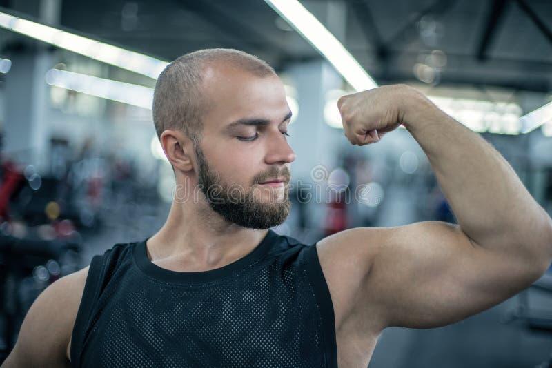 Stilig stark idrotts- man som upp pumpar bakgrund för begrepp för muskelgenomkörarebodybuilding Kroppsbyggare som visar muskler,  royaltyfria foton