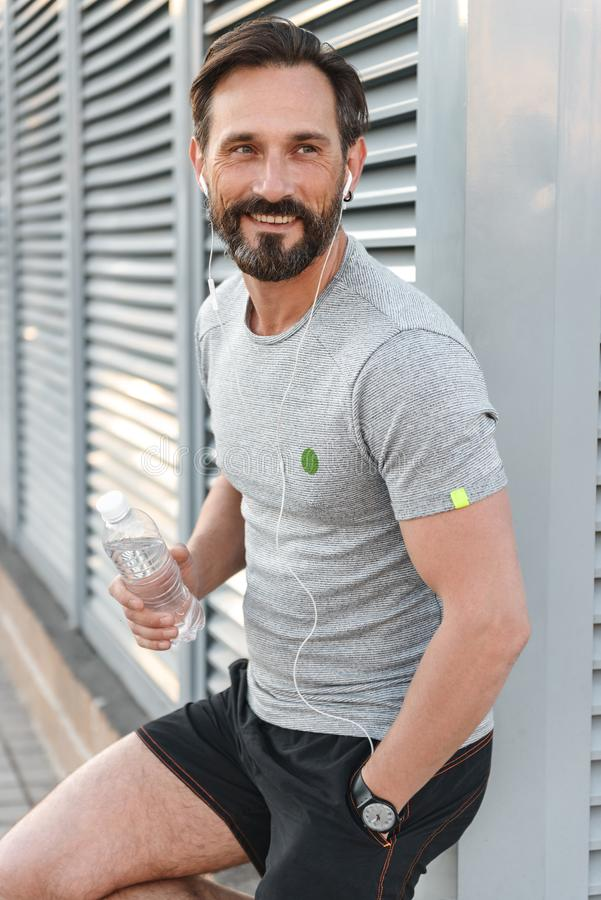 Stilig stark mogen idrottsman med hörlurar som rymmer flaskan med vatten fotografering för bildbyråer