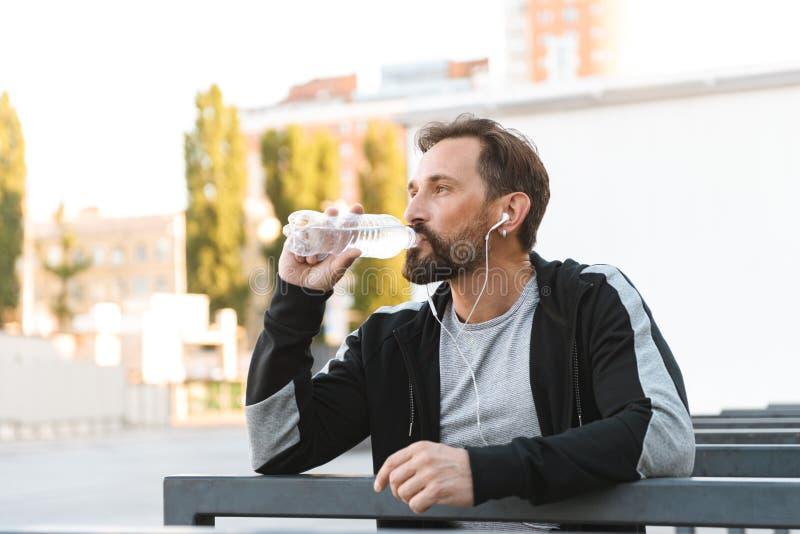 Stilig stark mogen idrottsman som dricker flaskan med vatten royaltyfria foton