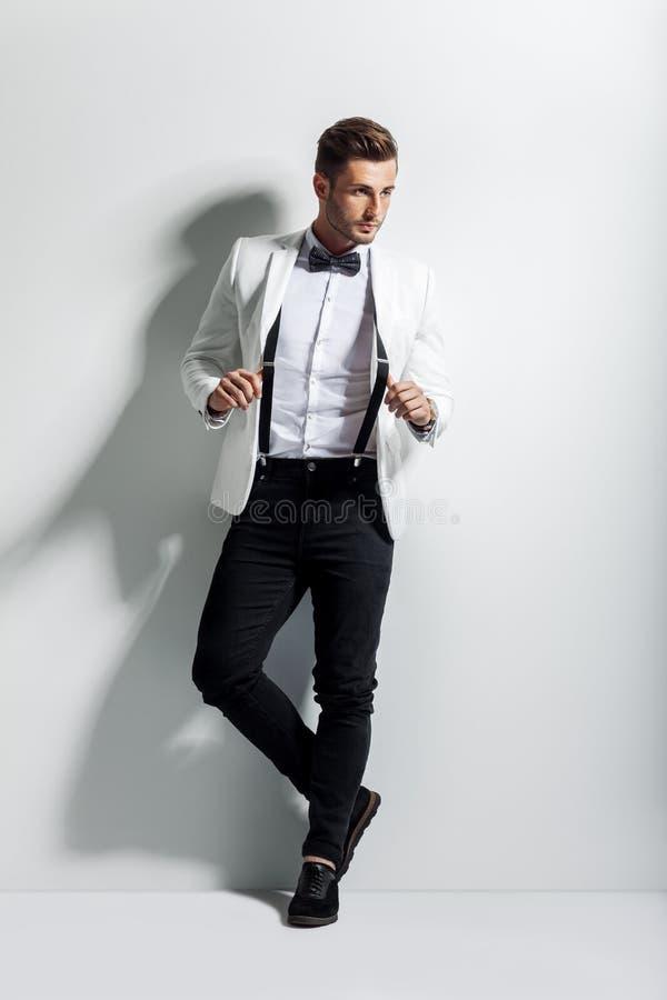 stilig stilfull man i den vita eleganta dräkten som poserar och lutar på väggen royaltyfria bilder