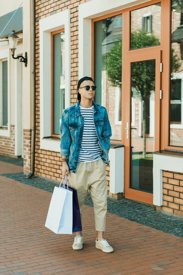 Stilig stilfull man i solglasögon som går med shoppingpåsar fotografering för bildbyråer