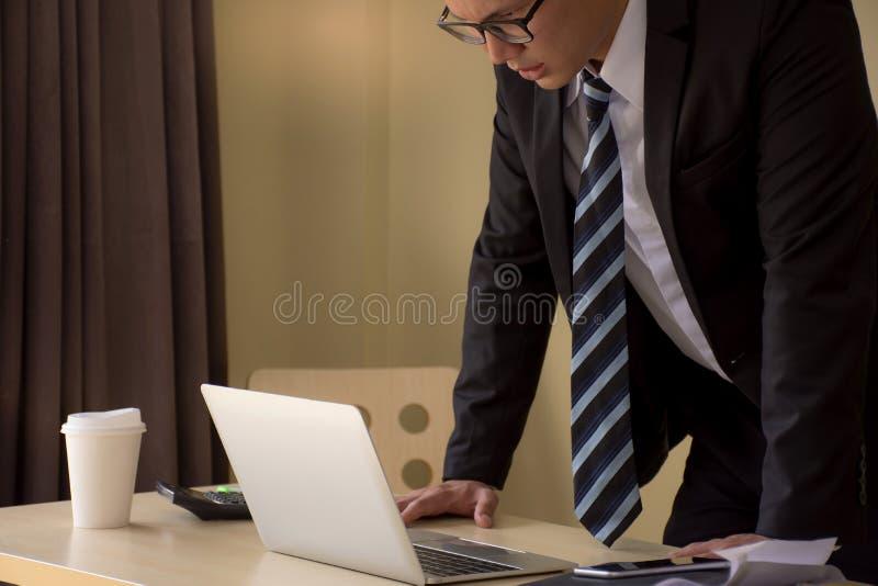 Stilig stressad ung asiatisk affärsman i exponeringsglas med bärbara datorn royaltyfria bilder