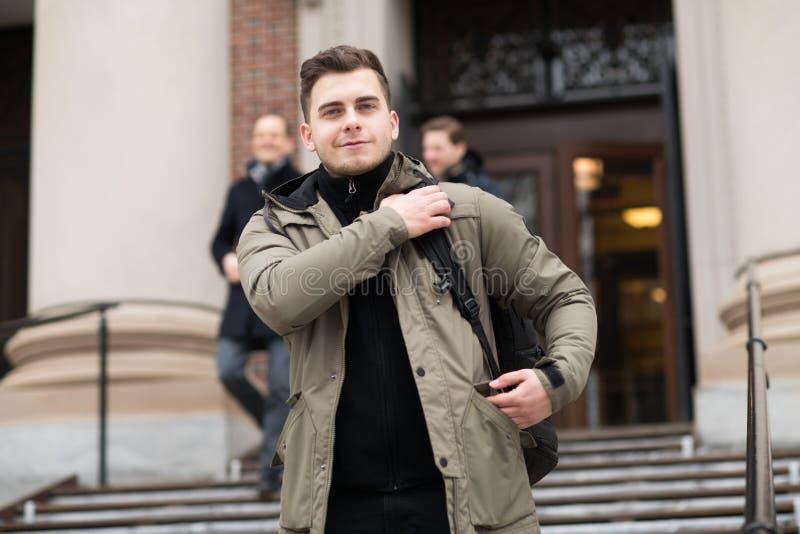 Stilig student som går i högskolauniversitetsområde med en ryggsäck till gruppen arkivfoton