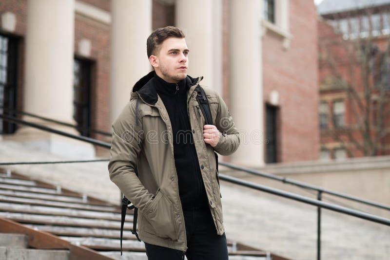 Stilig student som går på moment i högskolauniversitetsområde med en ryggsäck till gruppen royaltyfri bild