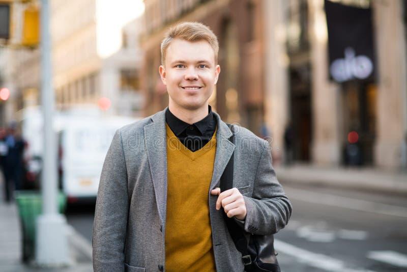 Stilig studentman med ryggsäckställningar på stadsgatan som ser kameran arkivbilder