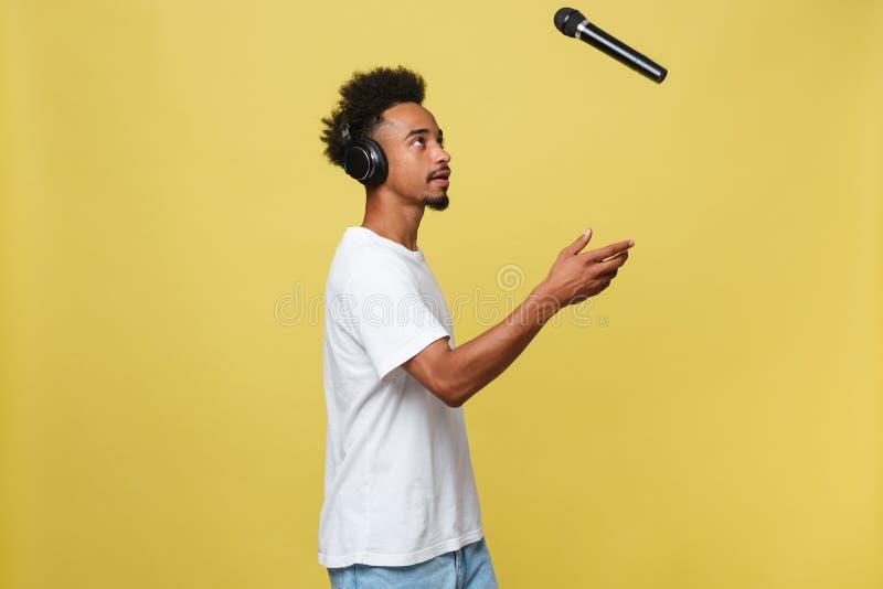 Stilig svart man som kastar en mikrofon och sjunga Isolerat över en gul bakgrund fotografering för bildbyråer