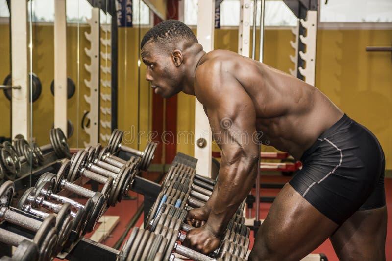Stilig svart manlig kroppsbyggare som vilar efter genomkörare i idrottshall fotografering för bildbyråer