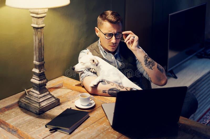 Stilig tatuerad man i glasögon som hemma arbetar på bärbara datorn, medan sitta på trätabellen med den gulliga hunden på hans royaltyfri foto