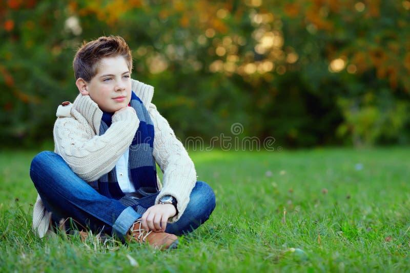 Stilig tonåringpojke på grönt gräs arkivfoto