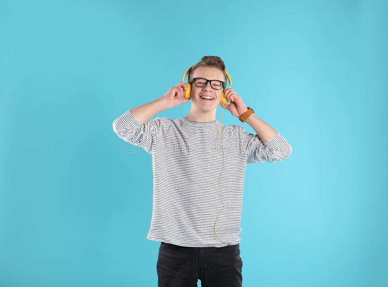 Stilig tonårs- pojke i exponeringsglas med hörlurar royaltyfri bild