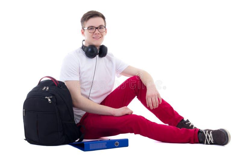 Stilig tonårs- pojke med ryggsäcken och hörlurar som sitter isolat arkivfoto