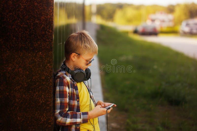 Stilig tonårs- pojke som lyssnar till musik och använder telefonen royaltyfria bilder