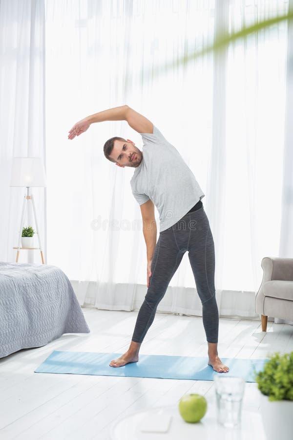 Stilig trevlig man som gör gymnastik arkivfoton