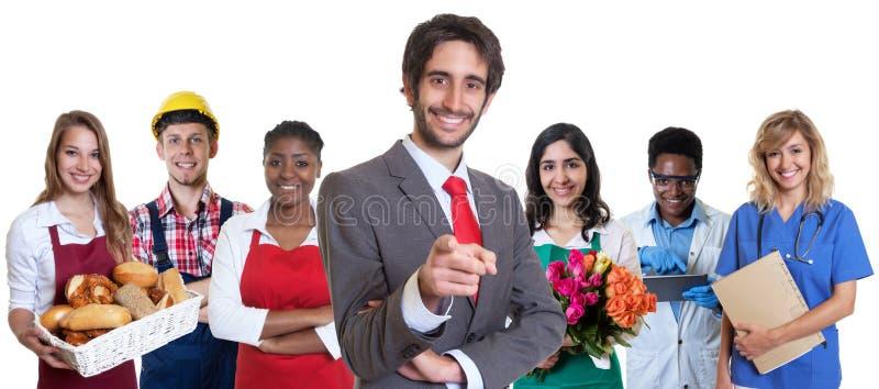 Stilig turkisk affärsdeltagare i utbildning med gruppen av latinska och afrikanska lärlingar royaltyfria bilder