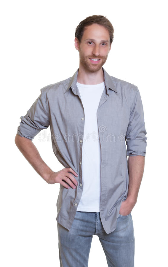 Stilig tysk grabb i grå skjorta med skägget i jeans royaltyfri foto