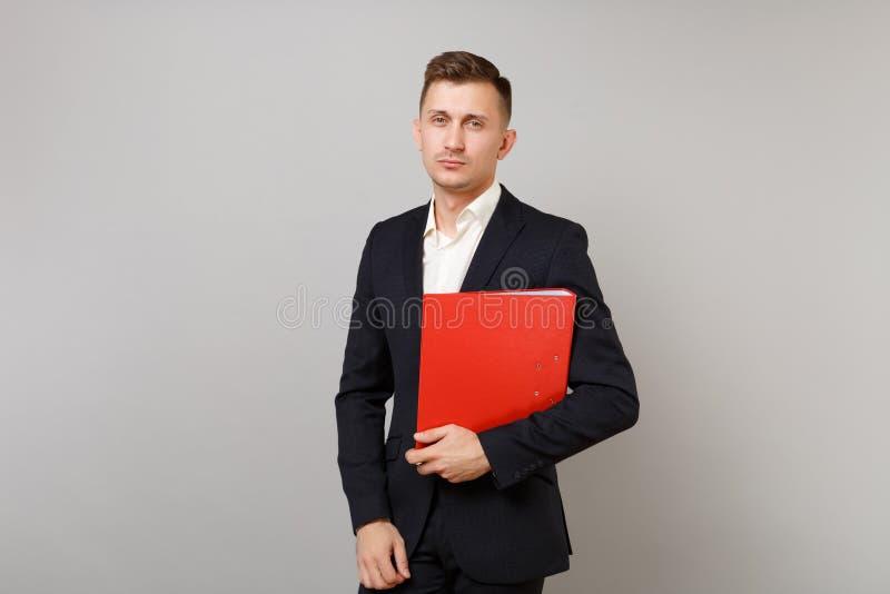 Stilig ung affärsman i den klassiska svarta dräkten, röd mapp för skjortahåll för legitimationshandlingardokumentet som isoleras  royaltyfri fotografi