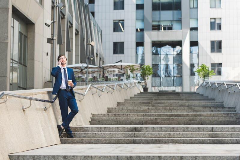 stilig ung affärsman i stilfull dräkt med kaffe som går samtal vid telefonen på trappa royaltyfri bild