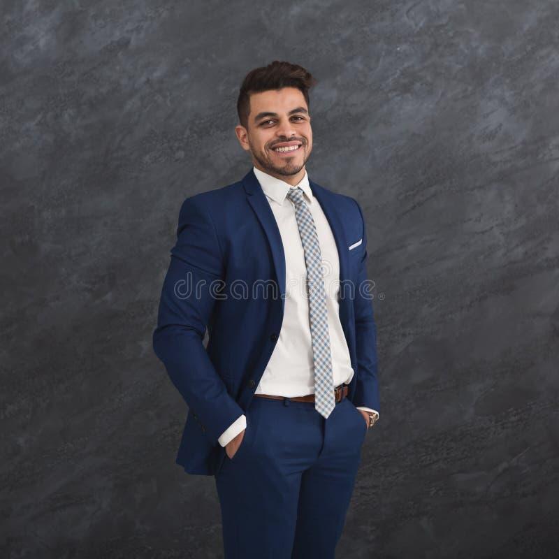 Stilig ung affärsman med handen i fack royaltyfri bild