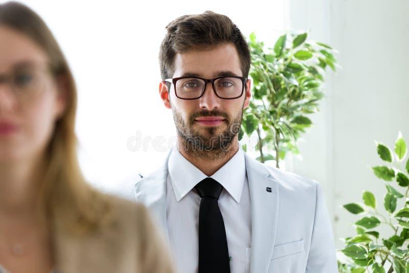Stilig ung affärsman med hans partner som ser kameran i ett hall av dem företag royaltyfri bild