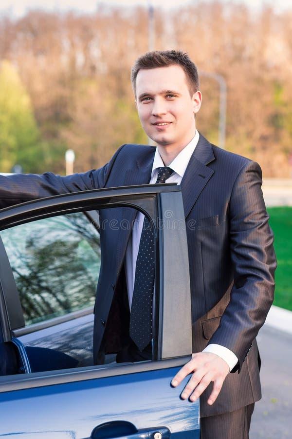 Stilig ung affärsman nära hans nya bil arkivbilder