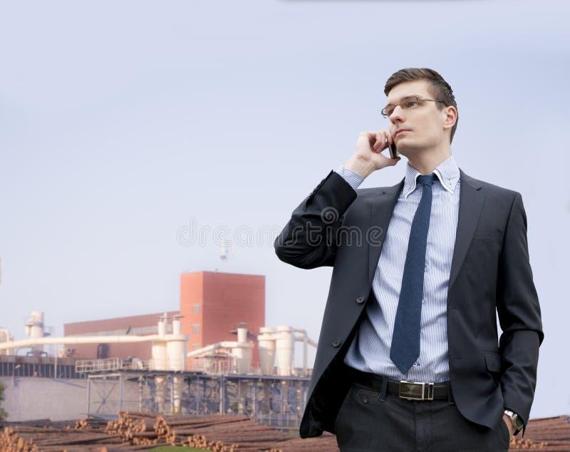 Stilig ung affärsman på industribyggnadbakgrunden royaltyfria foton