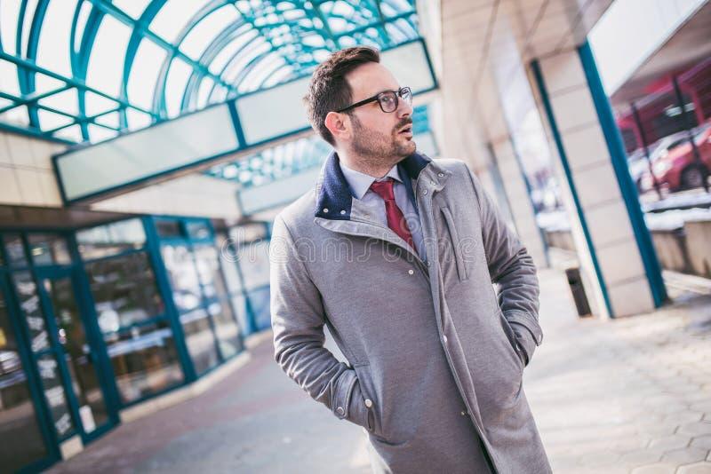 Stilig ung affärsman som framme går av byggnad royaltyfria bilder