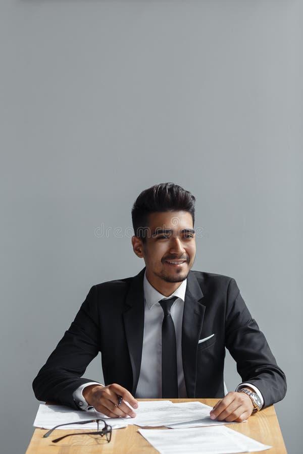 Stilig ung affärsman som ler, affärsman som arbetar med dokument som isoleras över grå bakgrund royaltyfri fotografi
