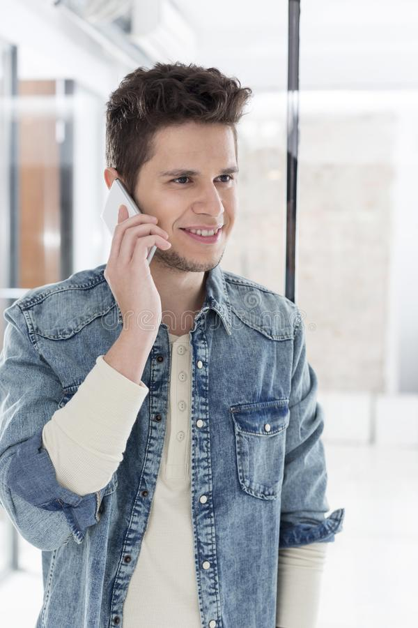 Stilig ung affärsman som talar på smartphonen på kontoret fotografering för bildbyråer