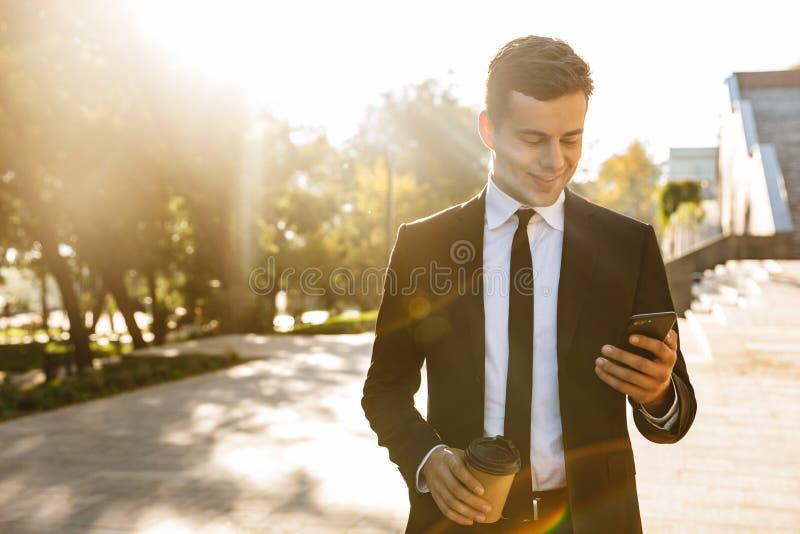 Stilig ung affärsman som utomhus går på gatan genom att använda mobiltelefonen royaltyfria foton