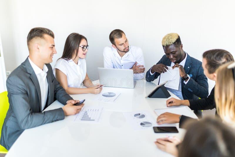 Stilig ung afrikansk amerikanaffärsman som framlägger diagram på ett möte med laget team arbete fotografering för bildbyråer