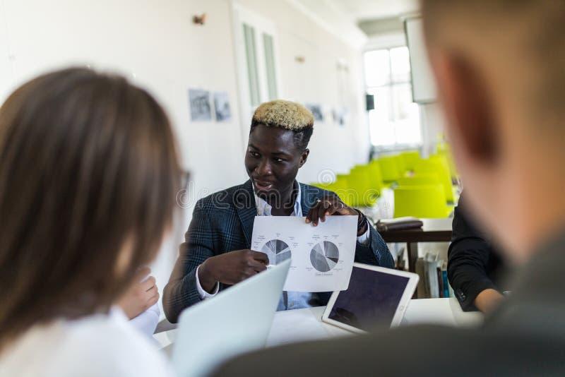 Stilig ung afrikansk amerikanaffärsman som framlägger diagram på ett möte med laget team arbete royaltyfri fotografi