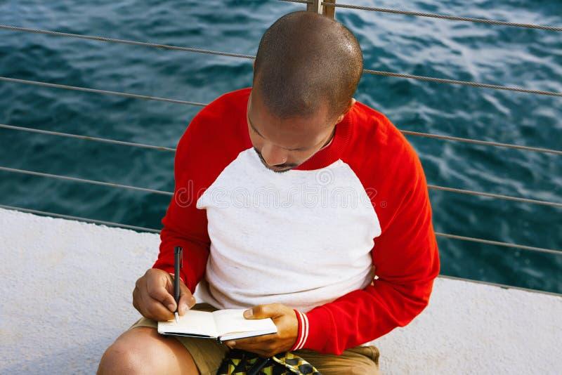 Stilig ung afrikansk amerikanhipsterman som kopplar av på stranden och gör textanmärkningar i pappers- anteckningsbok Blått hav p arkivbilder