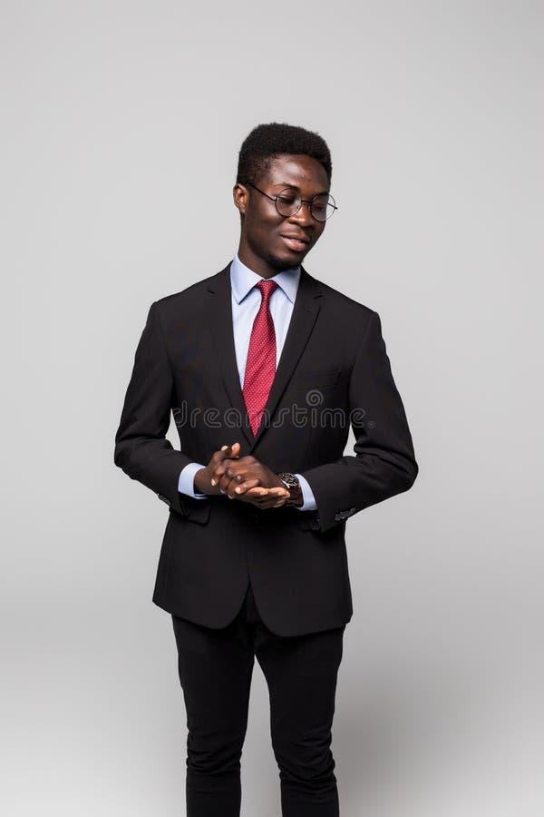 Stilig ung afrikansk man i dräkt, medan stå mot grå bakgrund arkivfoton