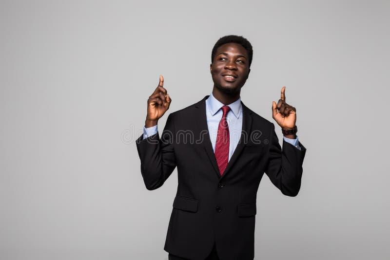 Stilig ung afrikansk man i dräkt som pekar upp och ler, medan stå mot grå bakgrund fotografering för bildbyråer
