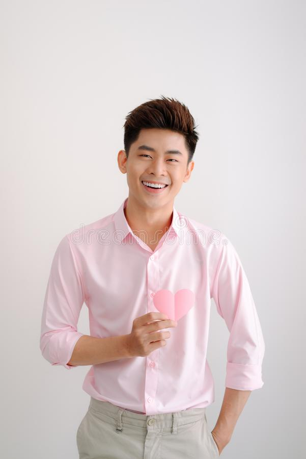 Stilig ung asiatisk hjärta för maninnehavpapper formade valentin royaltyfria bilder