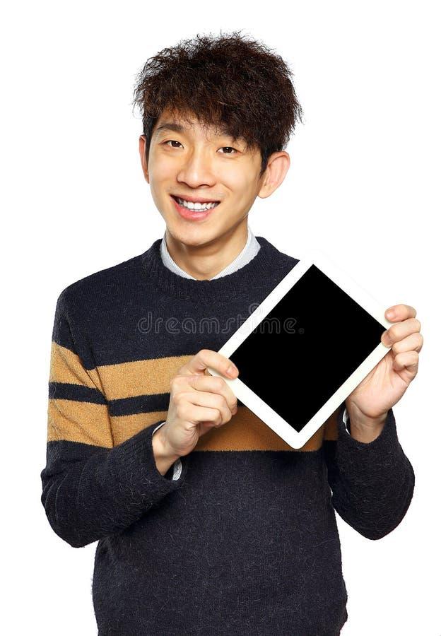 Stilig ung asiatisk man som använder minnestavlan/blocket arkivfoto