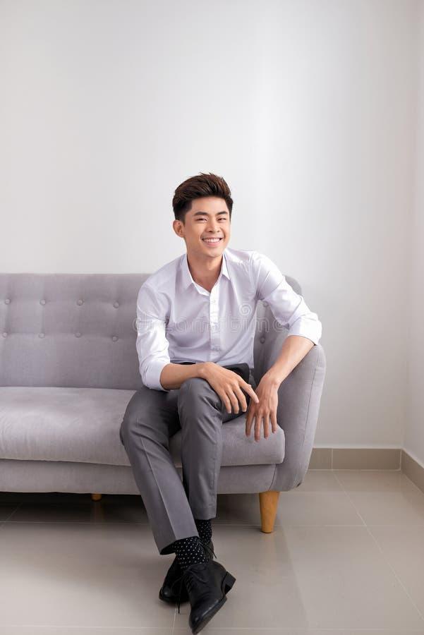 Stilig ung asiatisk man som hemma sitter på soffan, le som är lyckligt arkivfoton