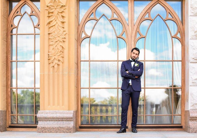 Stilig ung brudgum i elegant dräkt utomhus royaltyfri bild