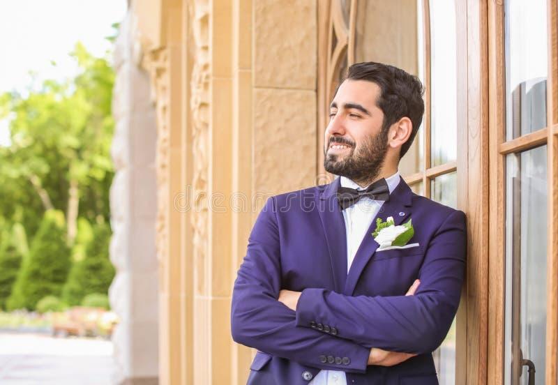 Stilig ung brudgum i elegant dräkt utomhus arkivbilder