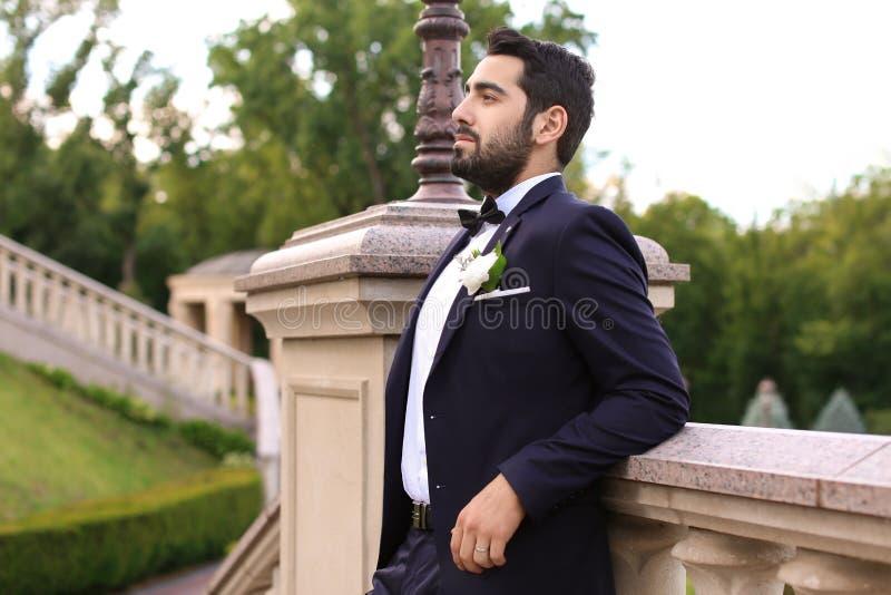 Stilig ung brudgum i elegant dräkt utomhus royaltyfri foto