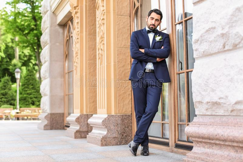 Stilig ung brudgum i elegant dräkt utomhus royaltyfria foton
