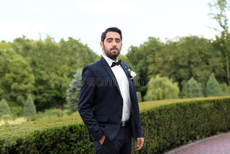 Stilig ung brudgum i elegant dräkt utomhus arkivfoton