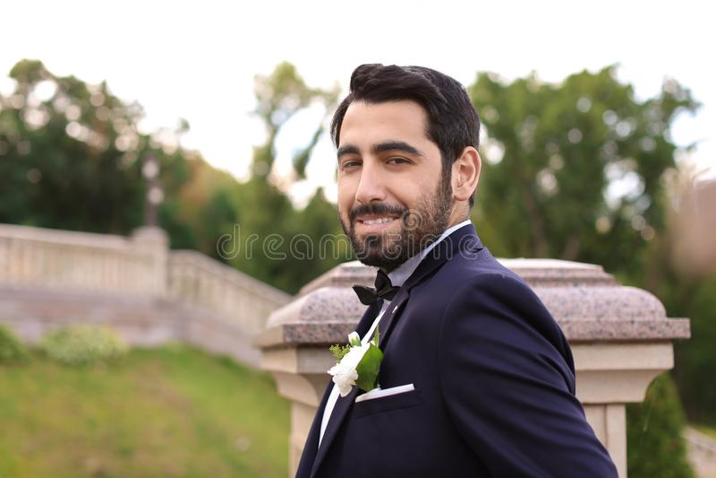 Stilig ung brudgum i elegant dräkt utomhus royaltyfria bilder